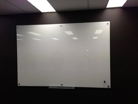 Glass Dry Erase Board in an Office Environment. Perfect glass surface white board. Professionally installed wall anchors for long term use